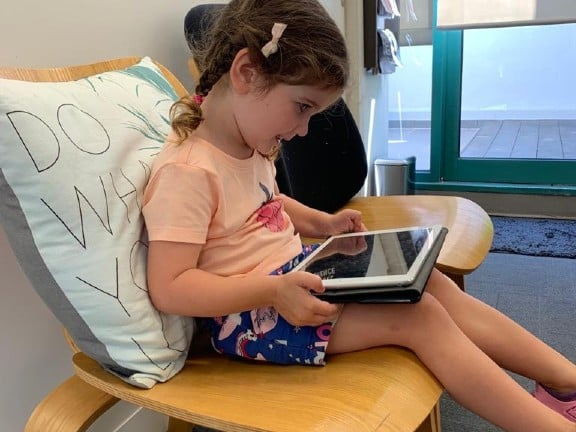 Little girl sitting and using an ipad