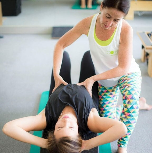 Physiotherapist helping with pilates exercise