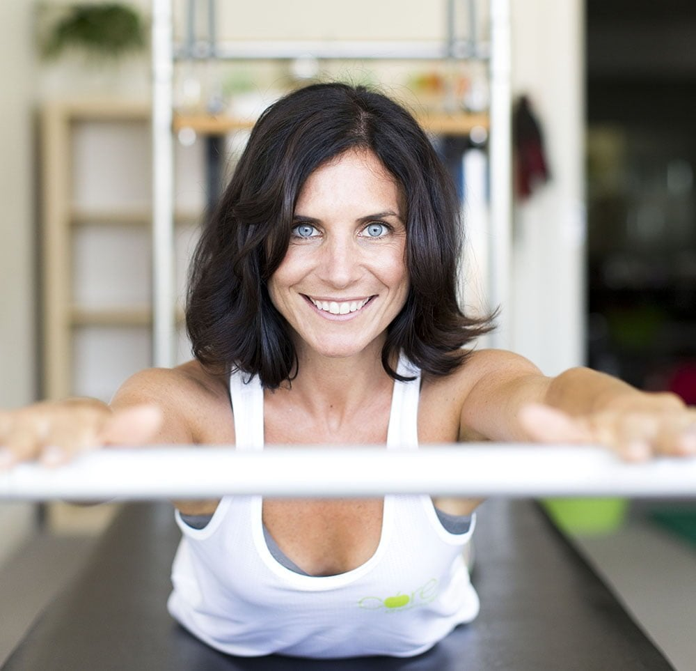 Woman smiling while doing core physio and pilates exercises